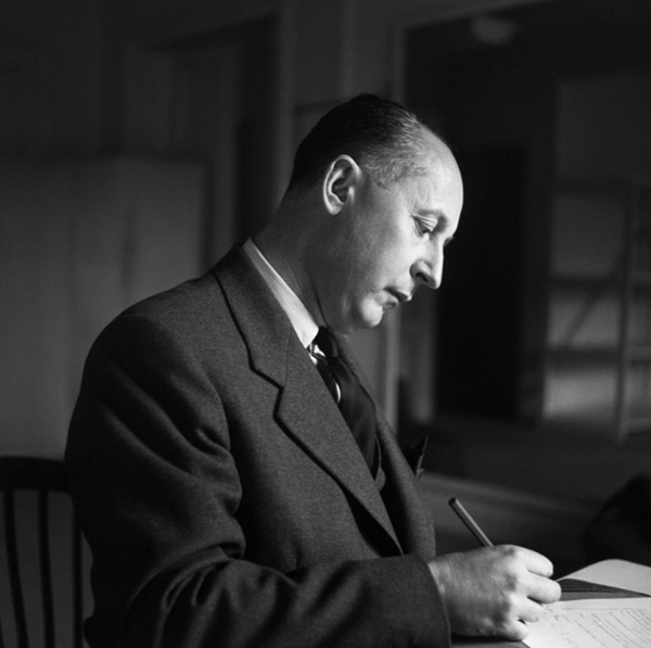 1950 --- Christian Dior Writing at Desk --- Image by © Bettmann/CORBIS