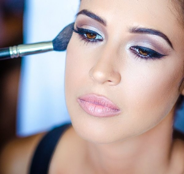 Makeup. Make-up Applying closeup. Cosmetic Powder Brush for Make up. Perfect Skin. On dark Background. Makeover