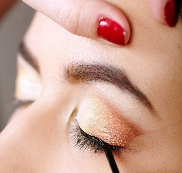 Closeup portrait of a beautiful woman having makeup applied