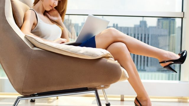 Young woman sitting on chair with laptop.