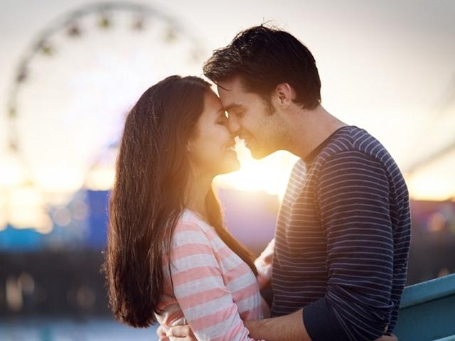 romantic couple in front of santa monica amusement park at sunset.